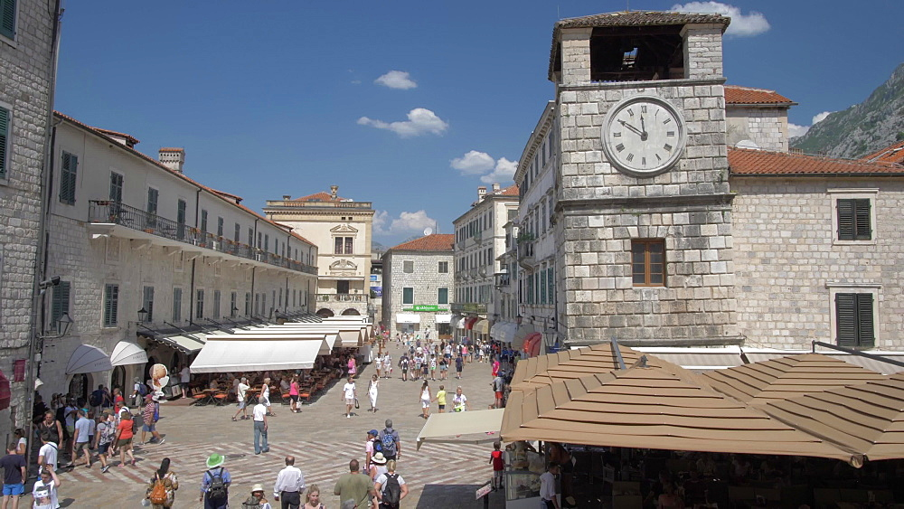 Shot through window of cafes and clock tower in Old Town of Kotor, UNESCO World Heritage Site, Kotor, Montenegro, Europe