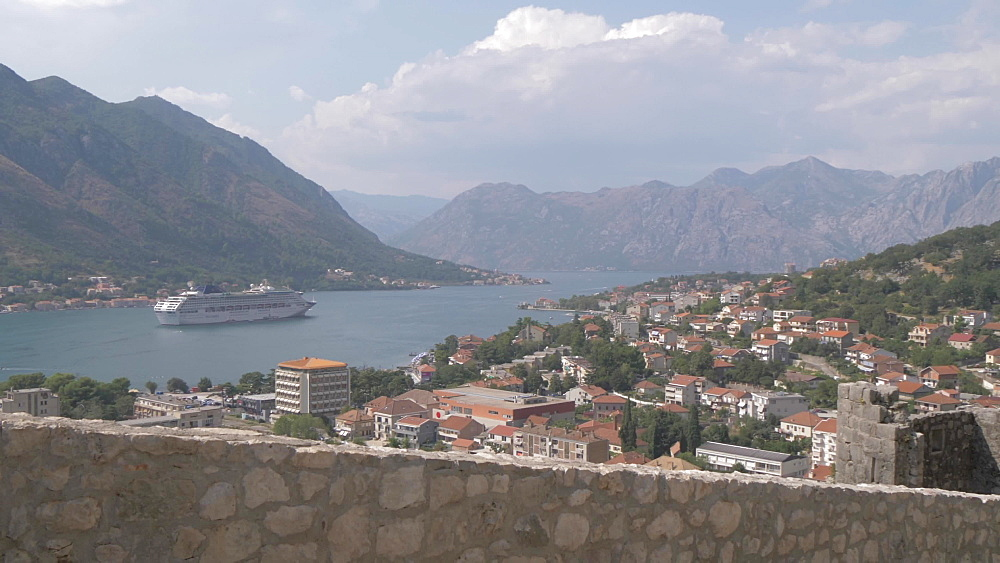 Tourists climbing steps above town and cruise ship in Bay of Kotor, Kotor, UNESCO World Heritage Site, Montenegro, Europe
