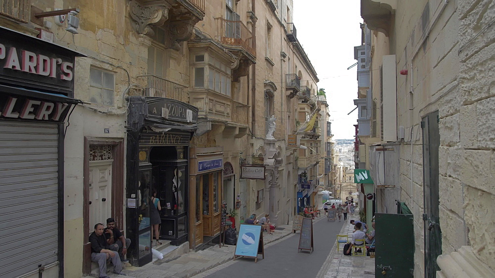Cafes and narrow street leading to harbour, Valletta, Malta, Mediterranean, Europe