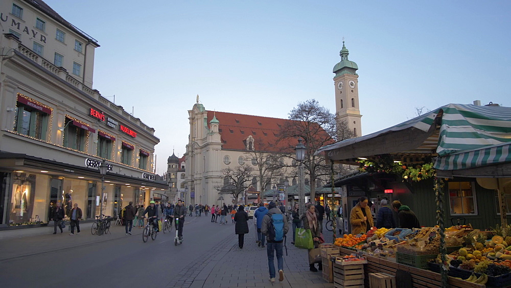 Pan shot of shops on Viktualienmakt and Heiliggeistkirche at Christmas, Munich, Bavaria, Germany, Europe
