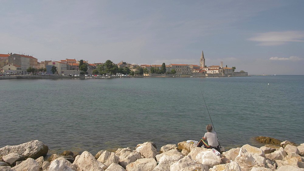 Crane shot of harbour fishing nets and man fishing in the harbour of Porec, Istra, Adriatic Sea, Croatia, Europe