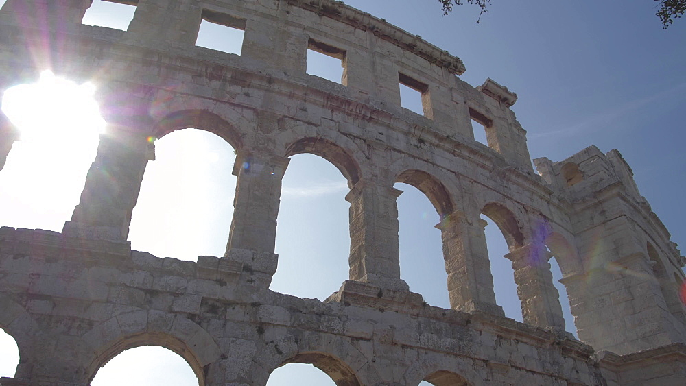 Sun breaking through the Amphitheatre against blue sky, Pula, Istria County, Croatia, Adriatic, Europe