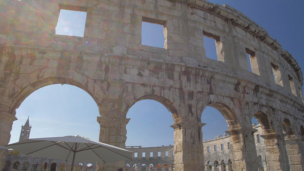 Tilt shot of cafe and the Amphitheatre against blue sky, Pula, Istria County, Croatia, Adriatic, Europe