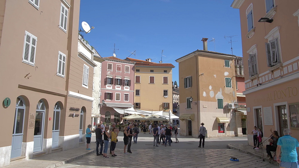Pan shot of pastel coloured buildings in the old town on sunny day, Rovinj, Istria County, Croatia, Europe