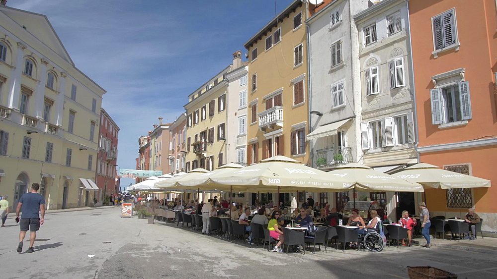 Pan shot of pastel coloured buildings and cafe in the old town on sunny day, Rovinj, Istria County, Croatia, Europe