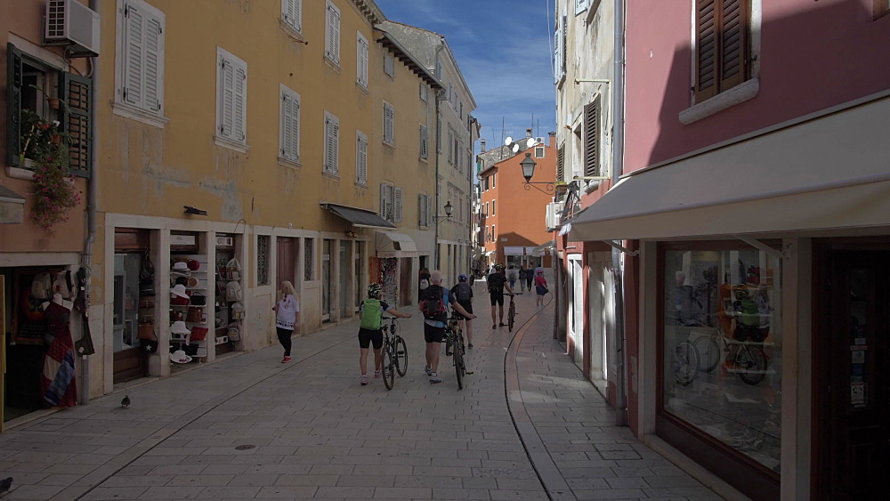 Cyclists on shopping street in the old town on sunny day, Rovinj, Istria County, Croatia, Europe