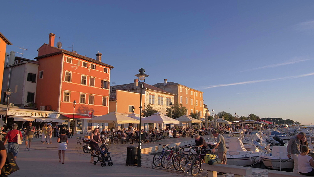 Pan shot of restaurants and cathedral of St. Euphemia and the old town at sunset, Rovinj, Istria County, Croatia, Europe