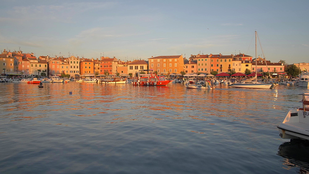 Pan shot of boat arriving in harbour of the old town at sunset, Rovinj, Istria County, Croatia, Europe