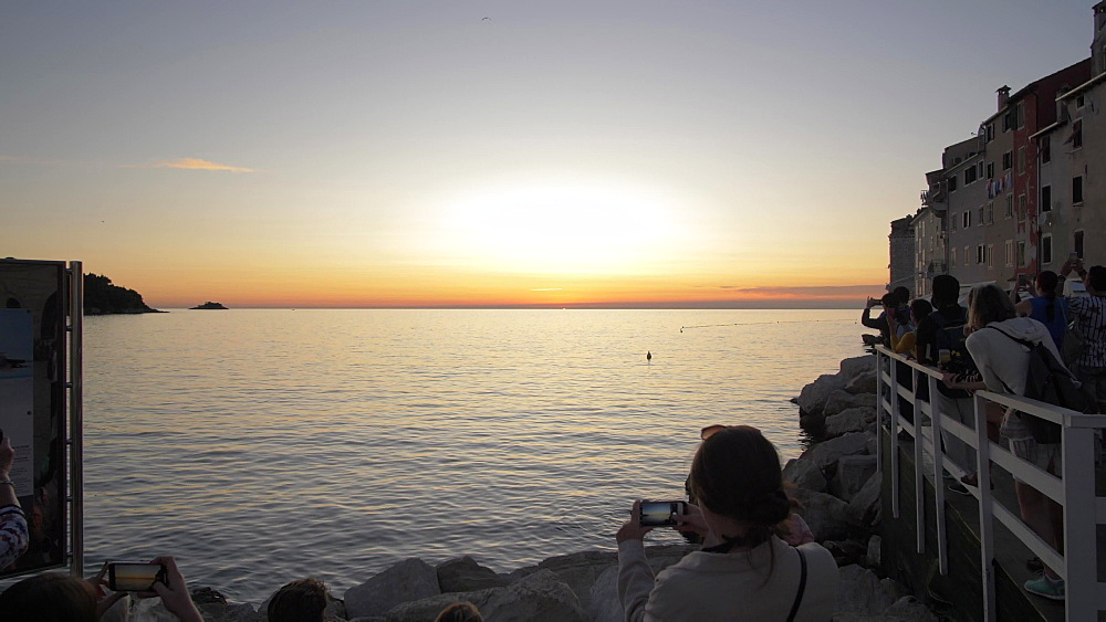 Shot of people overlooking the Adriatic Sea in the old town at sunset, Rovinj, Istria County, Croatia, Europe