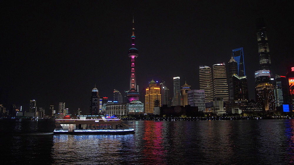 Pudong Skyline, illuminated cruise boat and Huangpu River from the Bund at night, Shanghai, People's Republic of China, Asia