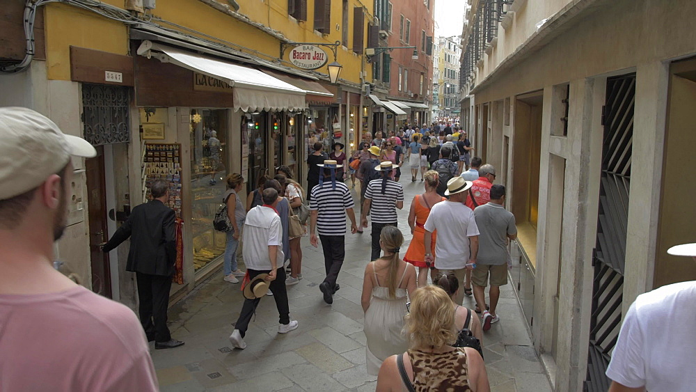 Tracking shot of people shopping and walking narrow streets in Venice, Venice, Veneto, Italy, Europe