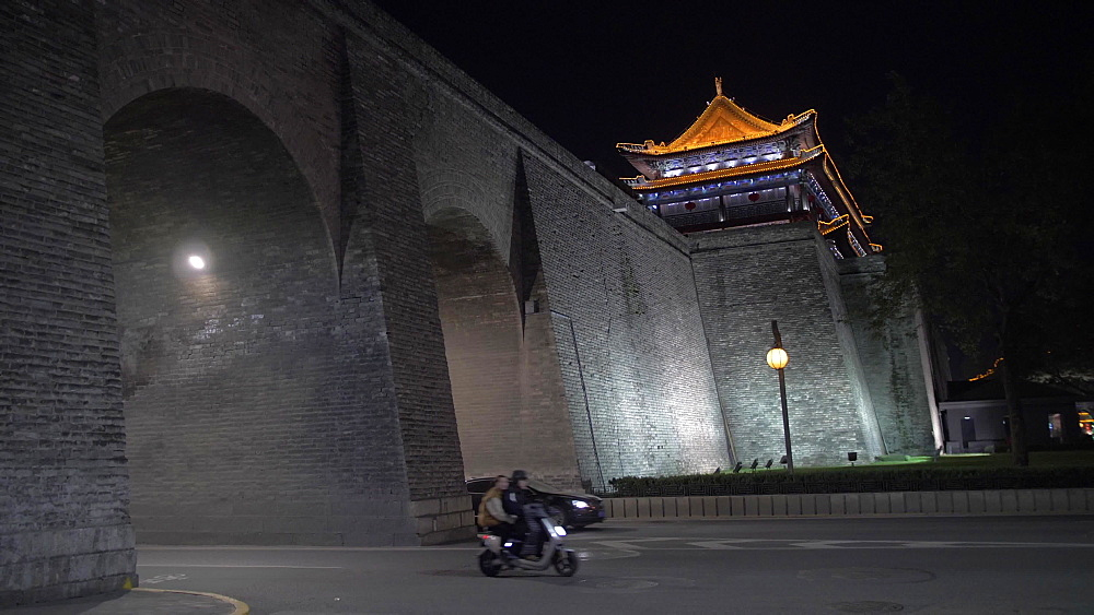 Traffic and ornate City Wall near Huan Cheng Gong Park at night, Xi'an, Shaanxi, People's Republic of China, Asia