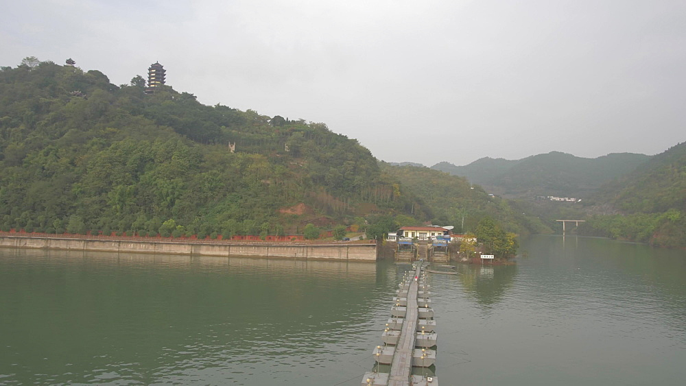 Pan shot of river bank and traditional Chinese pagoda on Yangtze River near Chongqing, People?s Republic of China, Asia