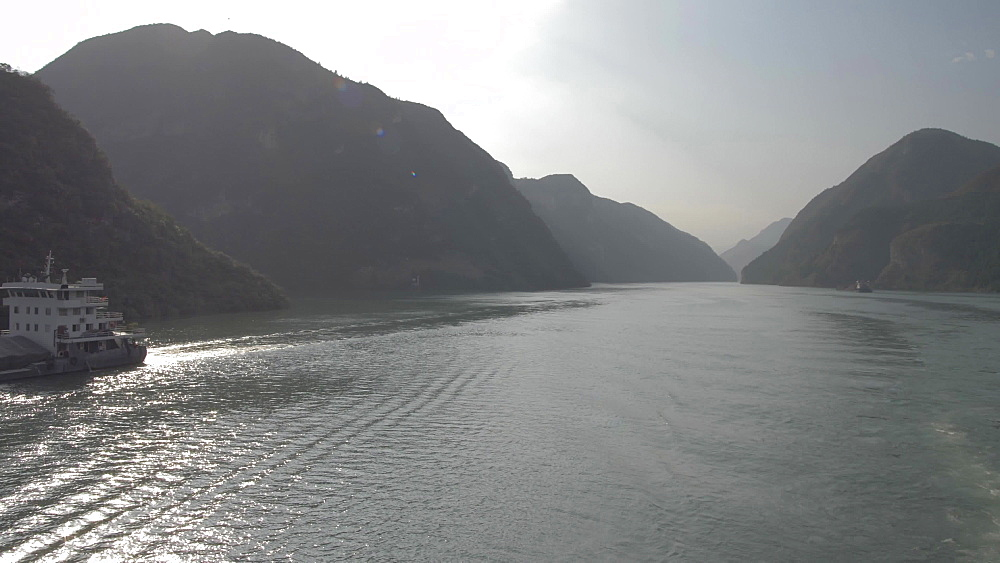 Tracking shot of barge on Yangtze River from onboard a cruise boat, Three Gorges, Yangtze River, People's Republic of China, Asia