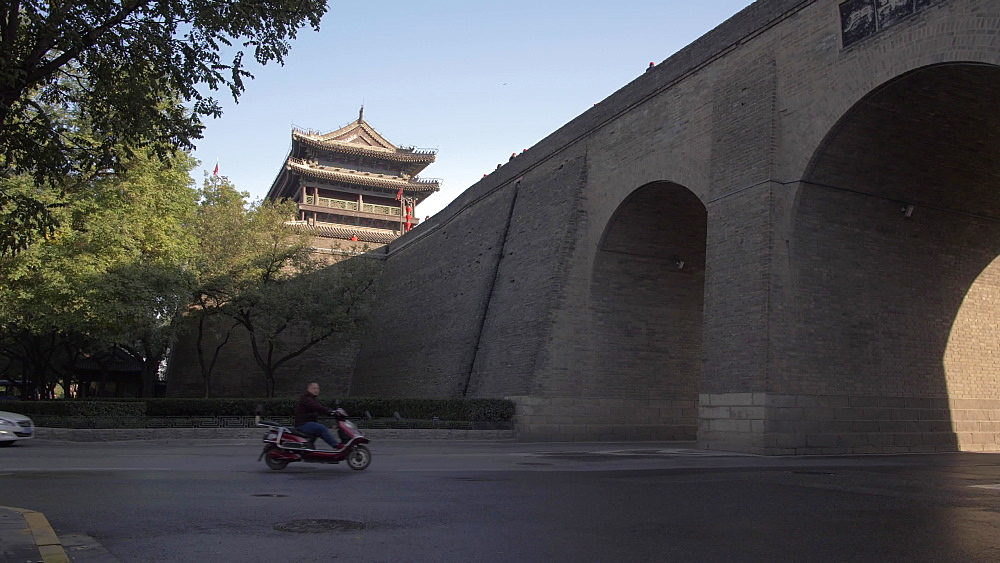 Slider shot of cyclists and traffic entering inner City Wall, Xi'an, Shaanxi, People?s Republic of China, Asia