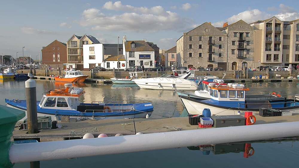 Boat passing by buildings and boats in North Quay, Weymouth, Dorset, England, United Kingdom, Europe