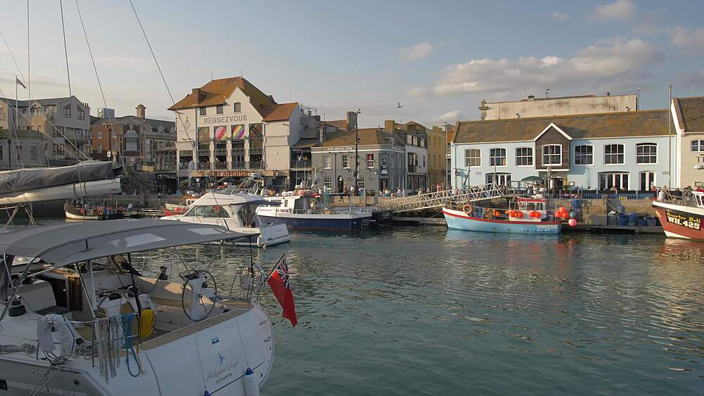 Buildings and boats in harbour at sunset, Weymouth, Dorset, England, United Kingdom, Europe