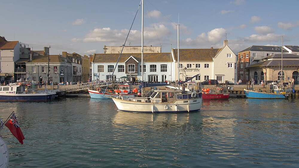 Boat passing by buildings and boats in harbour at sunset, Weymouth, Dorset, England, United Kingdom, Europe