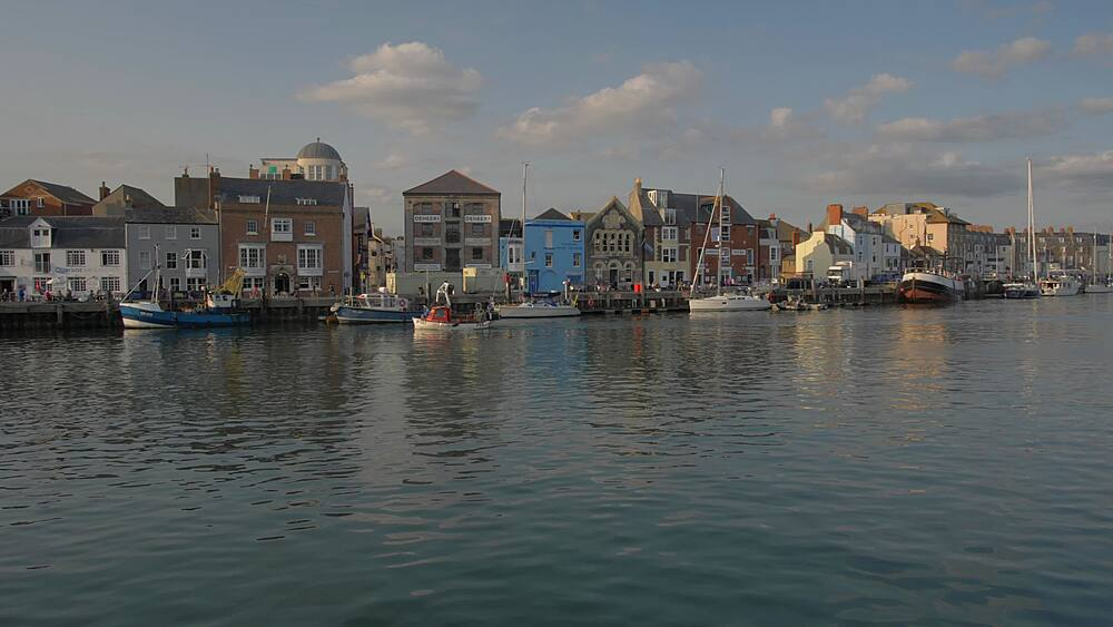 Pan shot of boat passing by buildings and boats in harbour at sunset, Weymouth, Dorset, England, United Kingdom, Europe