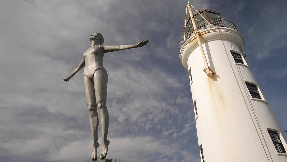 Old harbour lighthouse and Diving Belle sculpture, Scarborough, North Yorkshire, Yorkshire, England, United Kingdom, Europe