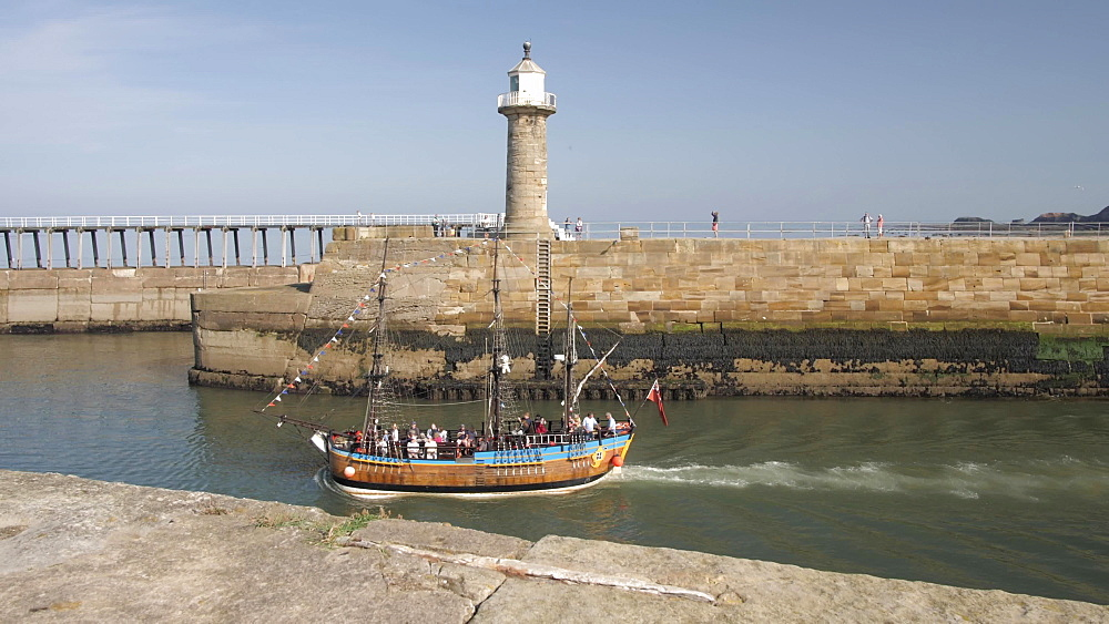 Tour boat on River Esk and lighthouse, Whitby, North Yorkshire, England, United Kingdom, Europe