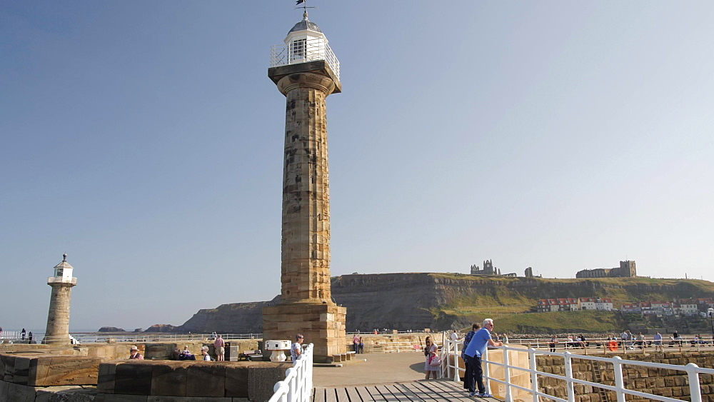 Lighthouse and St. Mary's Church in background, Whitby, North Yorkshire, England, United Kingdom, Europe