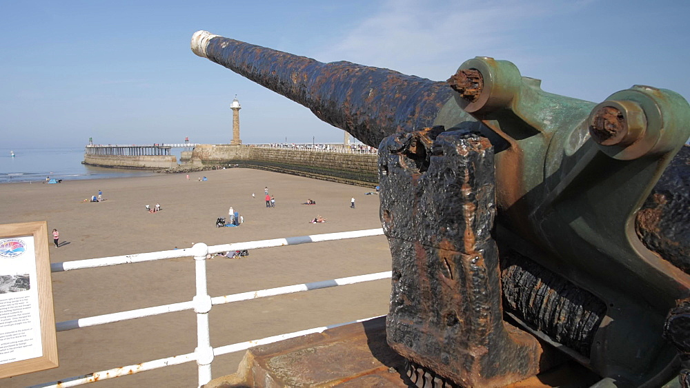 Cannon overlooking Whitby Beach and lighthouse, Whitby, North Yorkshire, England, United Kingdom, Europe
