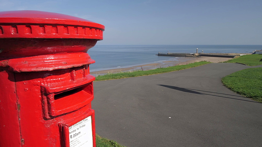 Red postbox and Whitby lighthouses from West Cliff, Whitby, North Yorkshire, England, United Kingdom, Europe