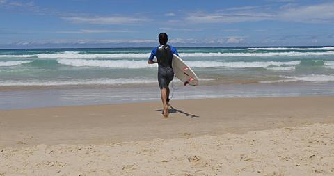 Surfer running into sea, Surfers Paradise, Gold Coast, Queensland, Australia