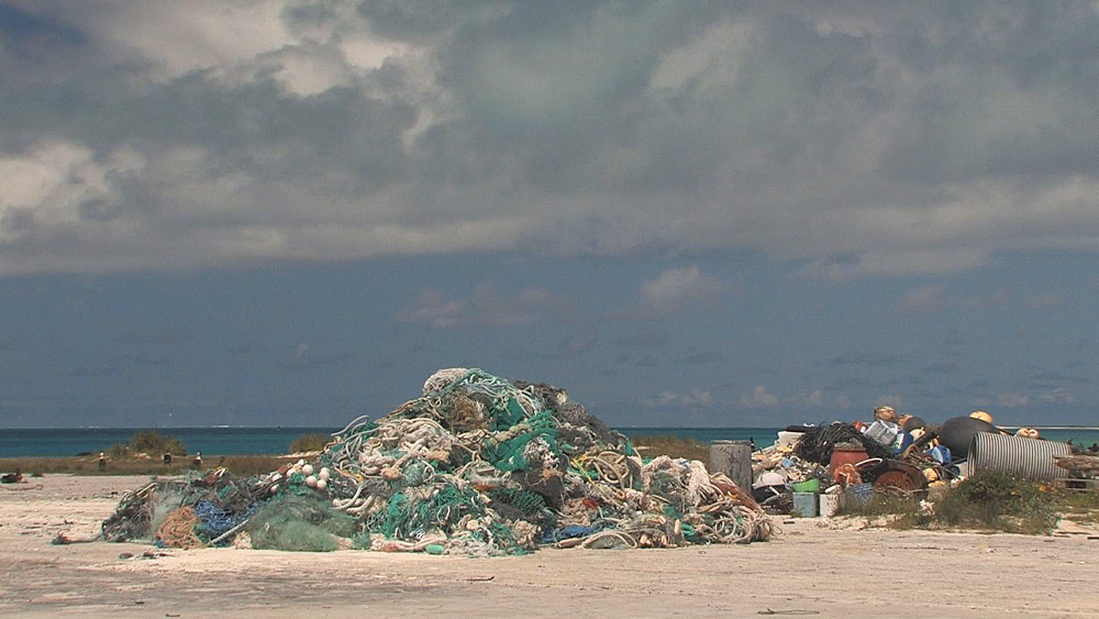 Mounds of washed up rubbish and discarded nets near beach. Conservation story - rubbish. Midway Island. Pacific
