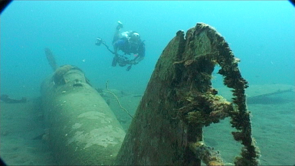WWII plane on sea floor, diver swims past and to camera.  Kimbe Bay, West New Britain, PNG - 981-251