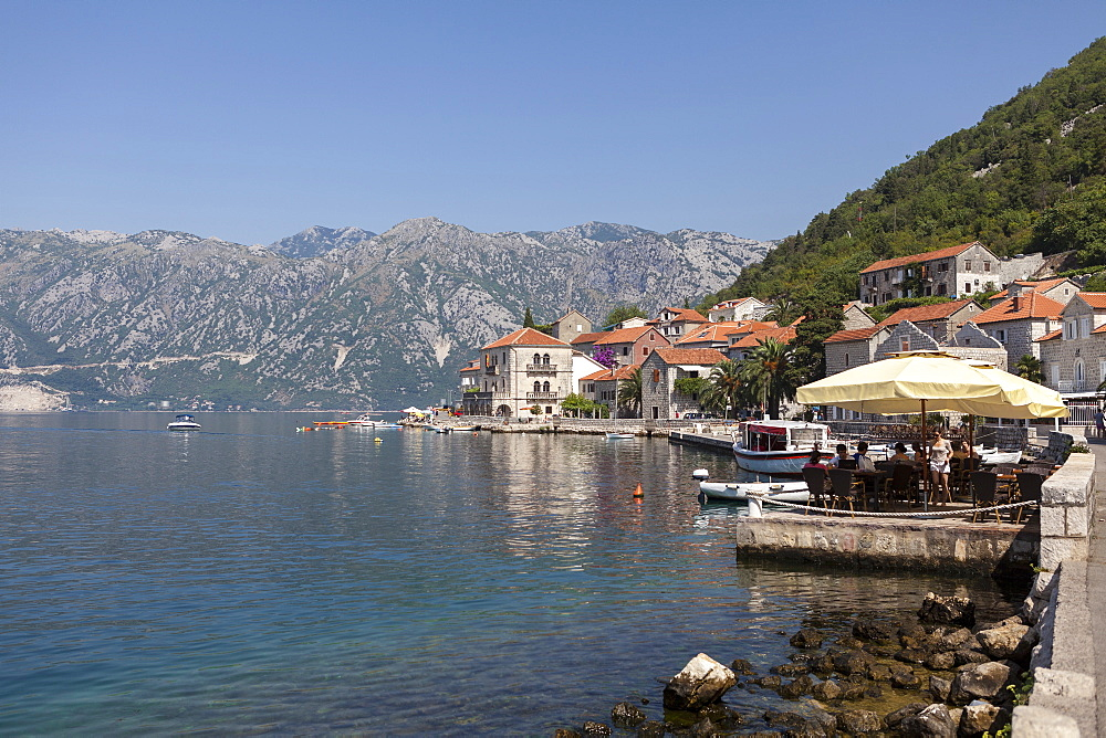 Perast harbour and promenade with tourists and inhabitants eating and drinking, Bay of Kotor, Montenegro, Europe