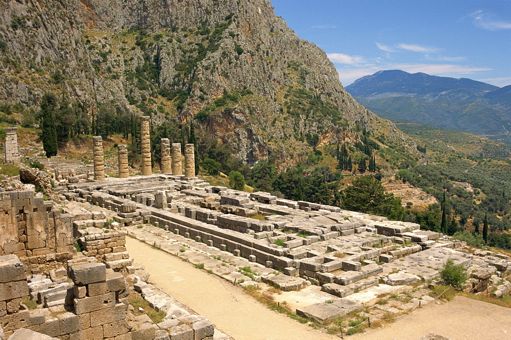 Ruins of the Temple of Apollo, with hills in the background, at Delphi, UNESCO World Heritage Site, Greece, Europe
