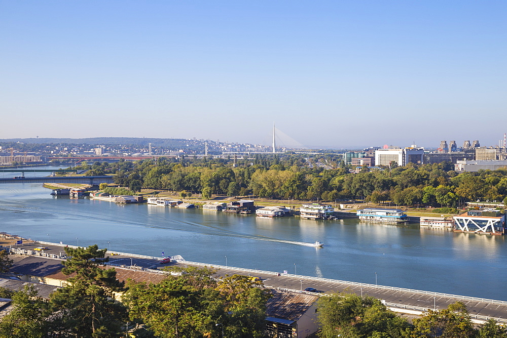 View of floating bars and nightclubs on Sava River, New Belgrade with Ada bridge in the distance, Belgrade, Serbia, Europe