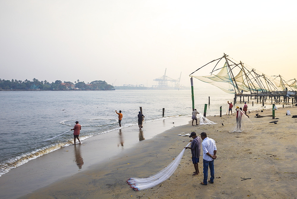 Fishermen on beach in front of Chinese fishing nets, Fort Kochi, Cochin (Kochi), Kerala, India, Asia