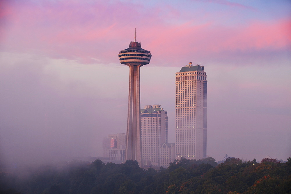 Mist from Horseshoe Falls swirling in front of Skylon Tower at dawn, Niagara Falls, Niagara, border of New York State and Ontario, Canada, North America