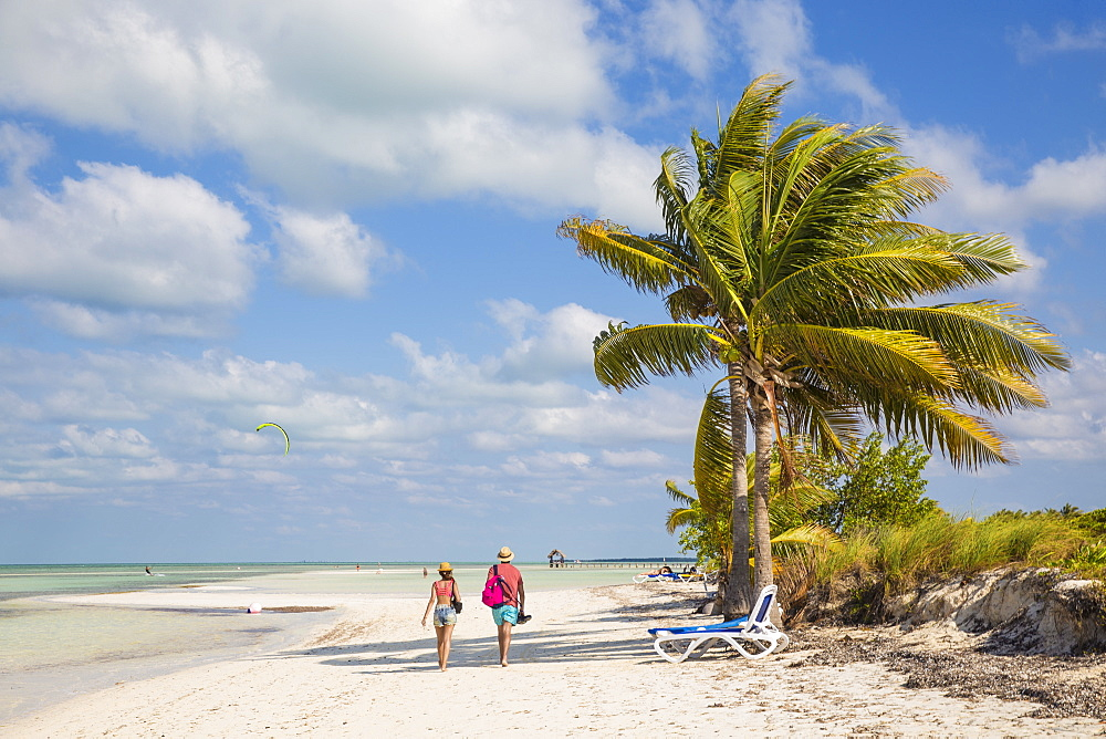 Couple walking along Playa El Paso, Cayo Guillermo, Jardines del Rey, Ciego de Avila Province, Cuba, West Indies, Caribbean, Central America