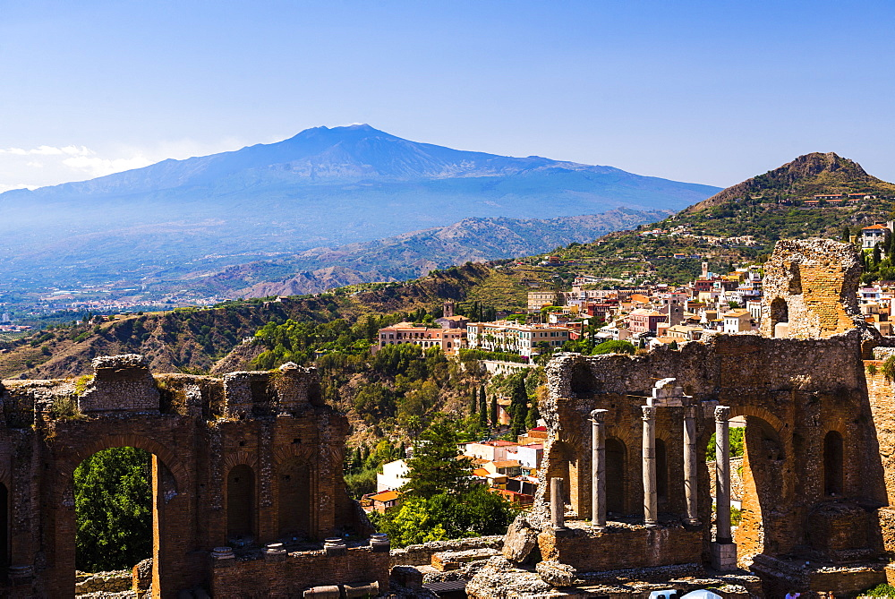 Mount Etna Volcano with ruins of Teatro Greco (Greek Theatre) in the foreground, Taormina, Sicily, Italy, Europe