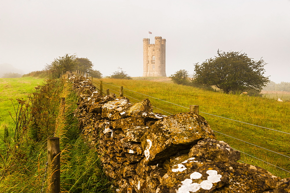 Misty sunrise at Broadway Tower, a National Trust property at Broadway, The Cotswolds, Gloucestershire, England, United Kingdom, Europe