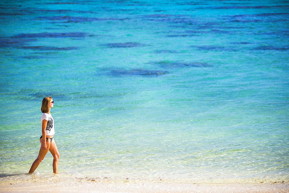 Woman walking along a tropical beach, Rarotonga Island, Cook Islands, South Pacific, Pacific