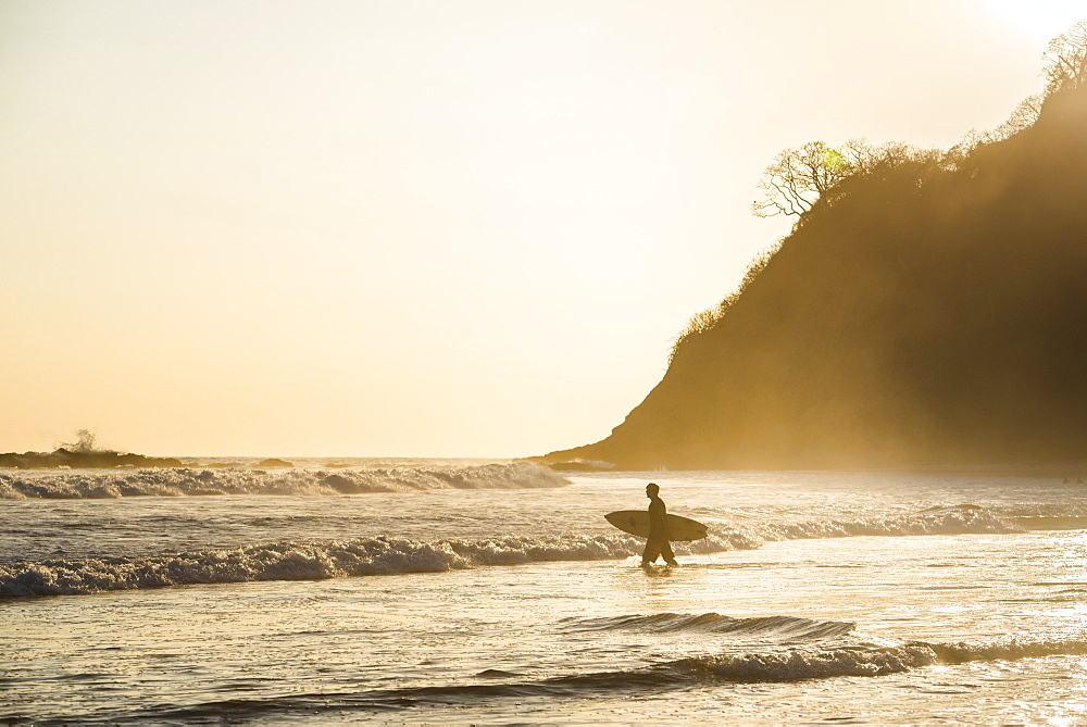 Surfers surfing on a beach at sunset, Nosara, Guanacaste Province, Pacific Coast, Costa Rica, Central America