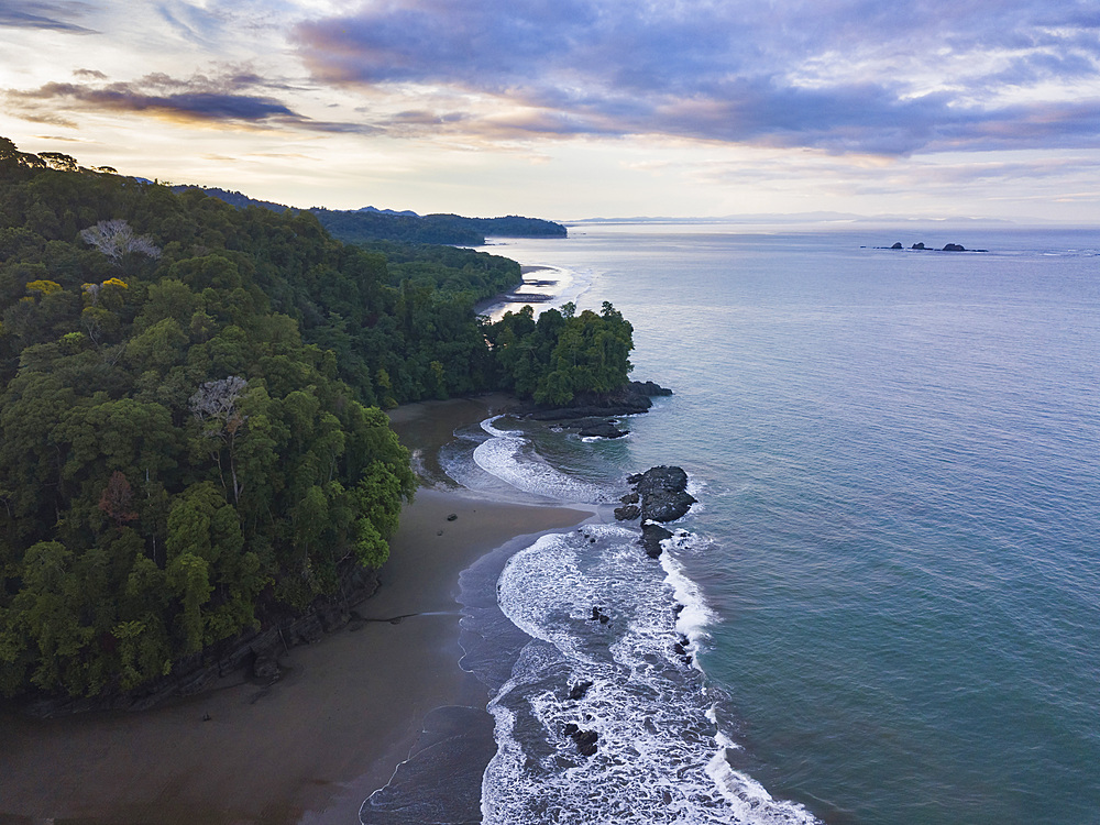 Drone view of Arco Beach and rainforest at sunrise, Uvita, Puntarenas Province, Pacific Coast of Costa Rica, Central America