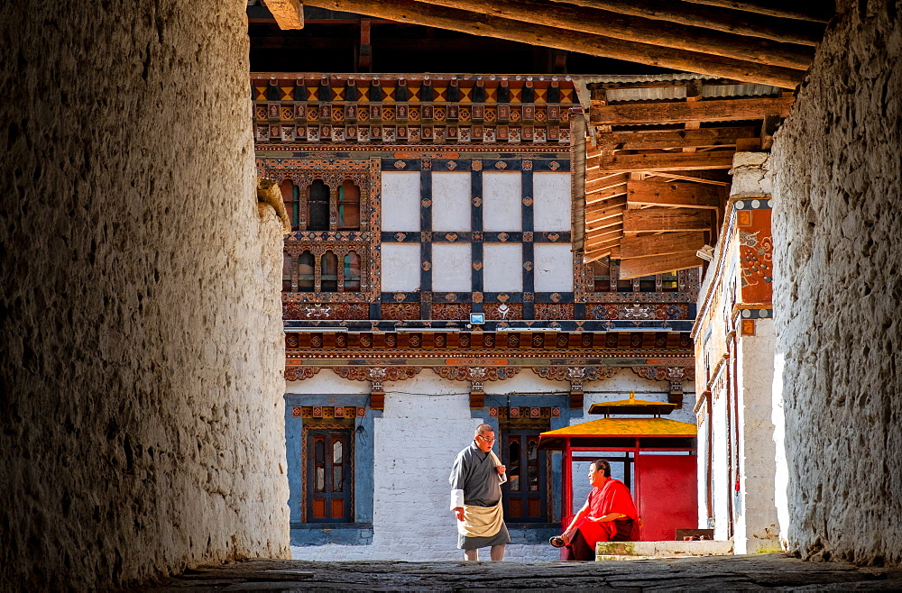 Two Buddhist monks talking inside monastery, Bhutan, Asia