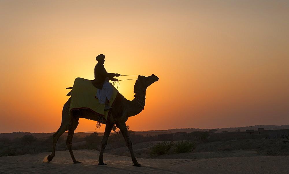 Camel and handler ride across Thar Desert at sunset, Osian.