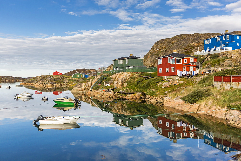 Calm waters reflect the brightly colored houses in Sisimiut, Greenland, Polar Regions