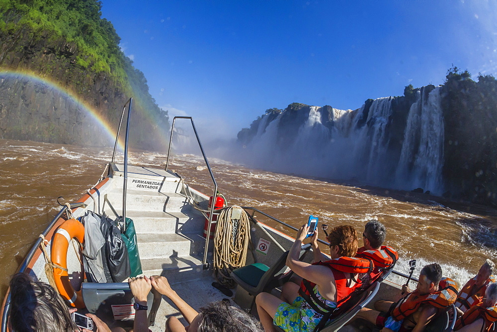 Tourists take a river boat to the base of the falls, Iguazu Falls National Park, UNESCO World Heritage Site, Misiones, Argentina, South America