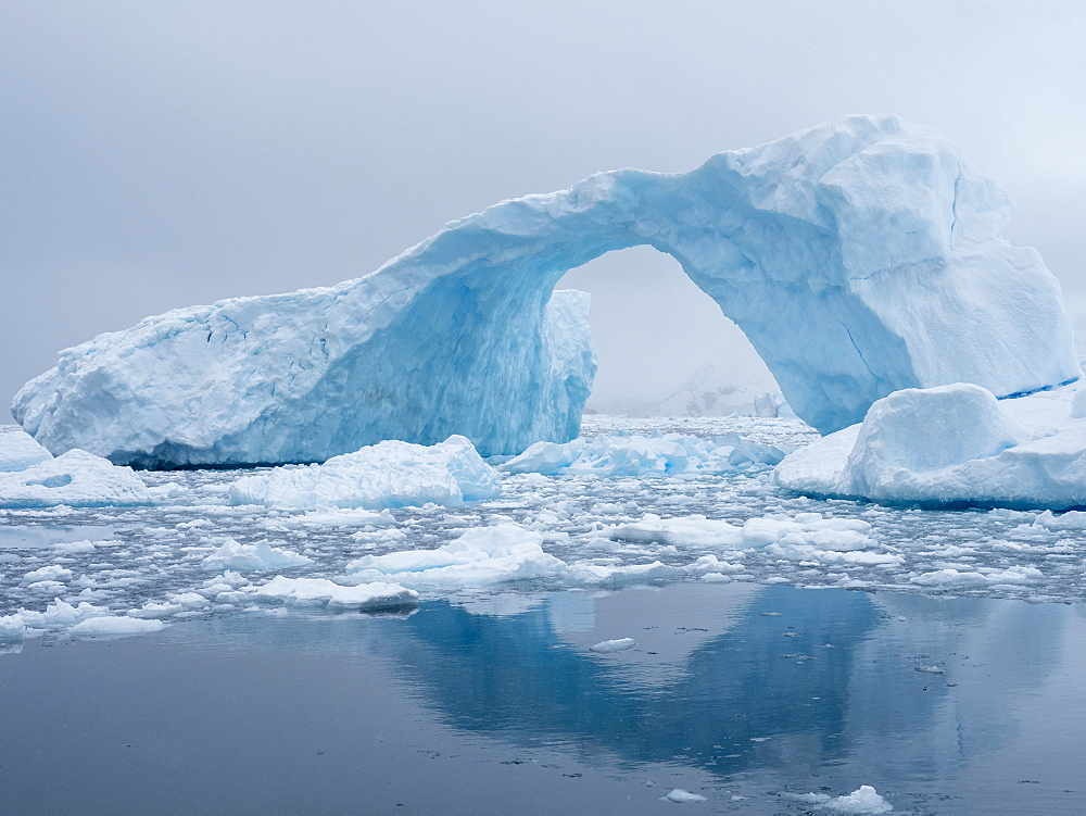 A huge arch formed in a tilted iceberg in Cierva Cove, Antarctica, Polar Regions