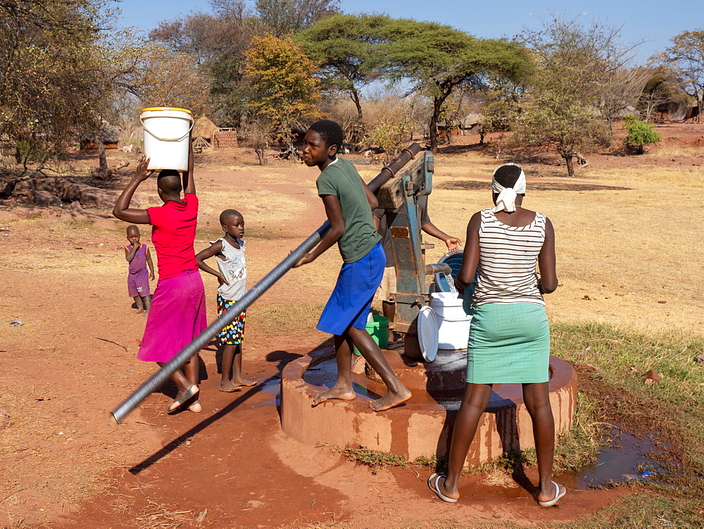 Pumping fresh water from a well in the fishing village of Musamba, on the shoreline of Lake Kariba, Zimbabwe, Africa