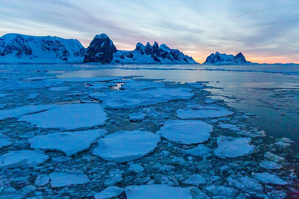 Sunrise on snow-covered mountains and dense sea ice in Neumayer Channel, Palmer Archipelago, Antarctica, Polar Regions - 1112-5818