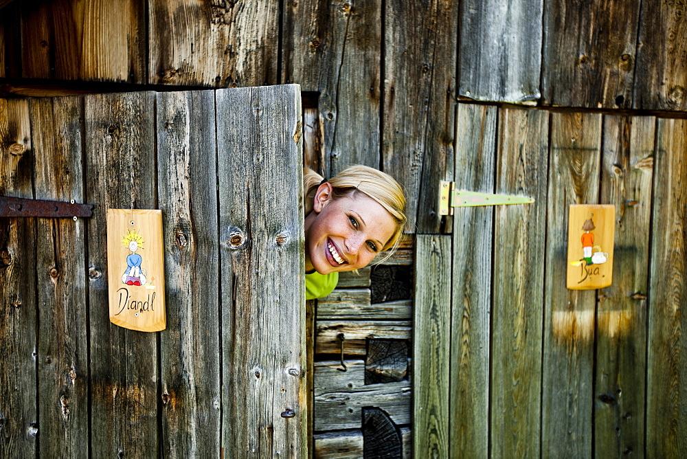 Young woman behind a ladies' room door looking at camera, lake Duisitzkar, Styria, Austria - 1113-104361
